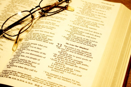 The family bible - opened at Psalms, reading glasses on page photo