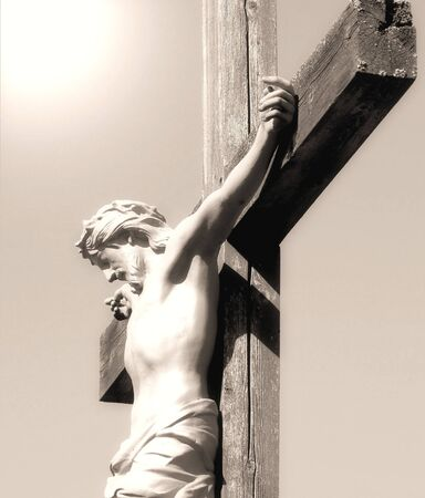 The Crucifixtion - Christ nailed to a wooden cross, light shines from above photo