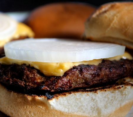 Juicy Cheeseburger Topped Off With An Onion Slice  Stock Photo
