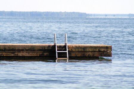 Swimming Dock Going Out Into Beautiful Blue Lake photo