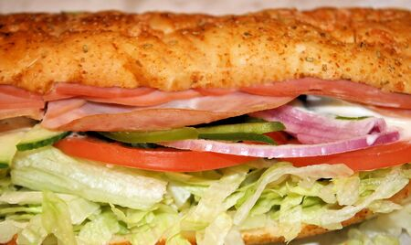 Sub sandwich stuffed with the works - cold cuts and veggies and creamy sauce photo