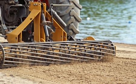 grader: Grader Sifting Sand On Public Beach Stock Photo