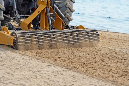sift: Grader Sifting Sand On Public Beach  Stock Photo