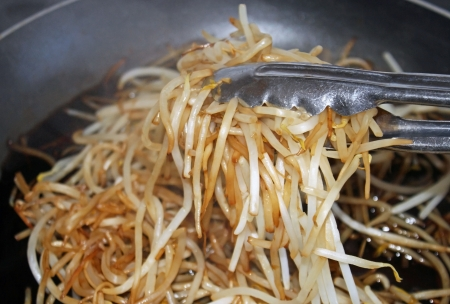 bean sprouts: Fresh bean sprouts cooking in soy sauce in skillet Stock Photo