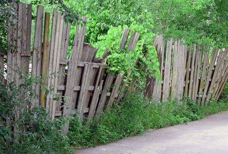An old worn wooden fence falling over and in need of repair photo