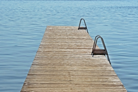 Long wooden dock reaching out over blue inviting waters