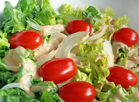 Fresh garden salad with ripe cherry tomatoes, sliced onions and creamy dressing photo