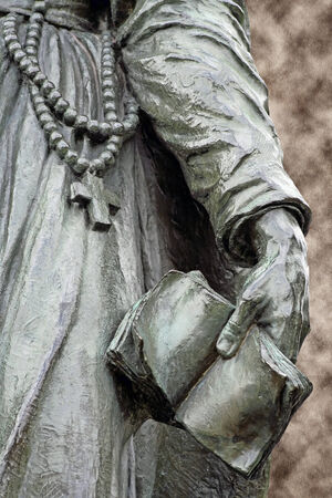 Bronze statue of a missionary priest  wearing a rosary and holding a bible in hand