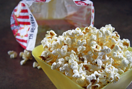 bowl of popcorn: A bowl of freshly popped microwaved popcorn