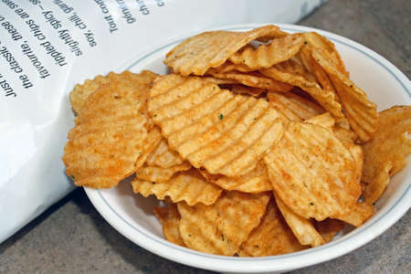 A bowl of spicy barbecued rippled potato chips beside bag photo