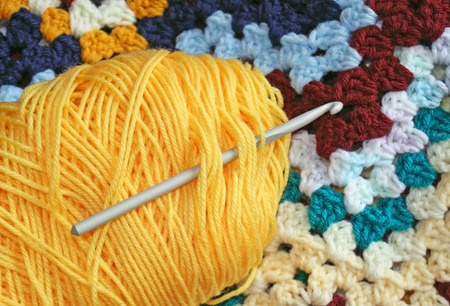 skein: Skein of yarn in yellow gold with crochet hook - granny square project in background