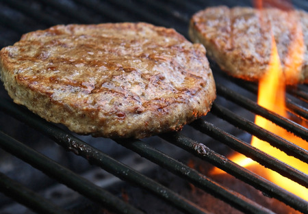 grill: Burgers Cooking Over Flames On The Grill