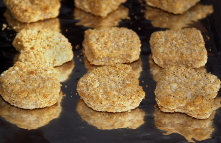 foil: Frozen chicken nuggets on foil cooking in oven
