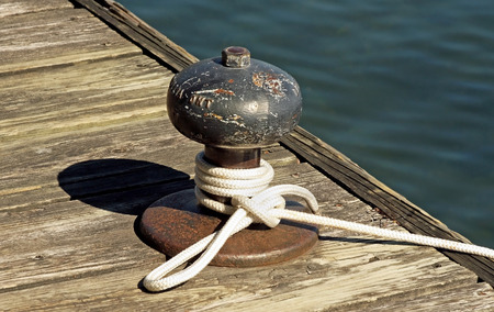 knotting: Rope tied to a metal boat slip at dock