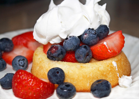 Fresh ripe blueberries and strawberries on a fat free sponge cake topped off with low calorie fluffy whipped cream photo