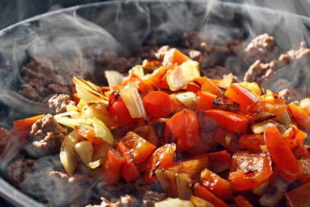 ground beef: Lean ground beef cooking in skillet with diced red peppers and onions