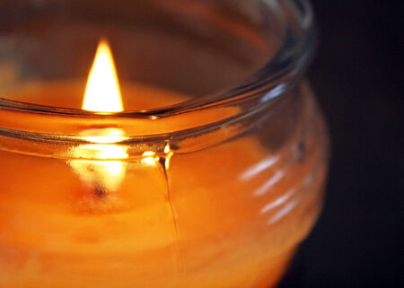 candle: Flame glowing in a scented jar candle Stock Photo