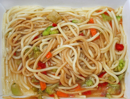 Cardboard container of noodles and vegetables that has been microwaved photo