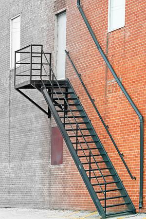 huir: Escalera de metal escalera de incendios en el exterior del edificio de ladrillo desvaneci�ndose en gris Foto de archivo