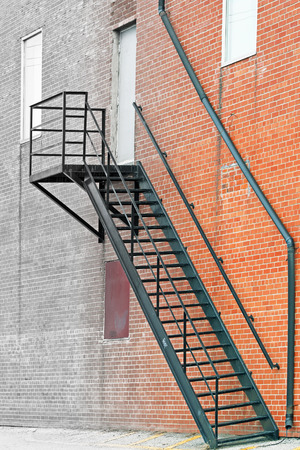fire escape: Metal stair fire escape on exterior of brick building  fading into gray