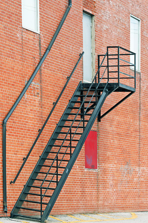 fire escape: Metal stair fire escape on exterior of brick building