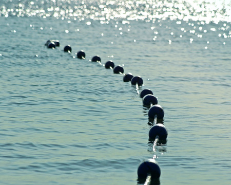 buoys: Buoys strung together on beautiful blue sparkling waters in early morning.  Safety buoys to create safe swimming area for swimmers Stock Photo