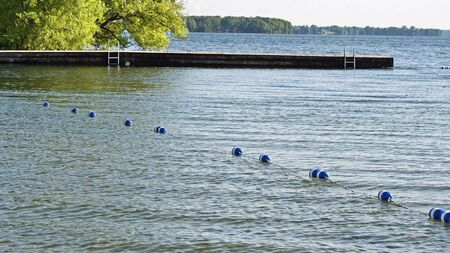 floaters: Buoys strung together by rope along beautiful blue lake to create safe swimming area for swimmers. Dock with ladders in background