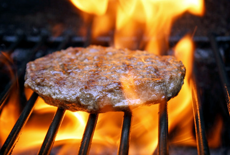 sizzling: Juicy beef burger sizzling over hot flames on the barbecue