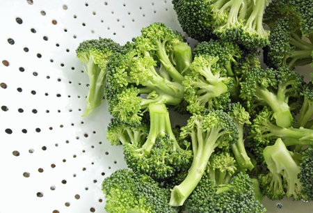 cut up: Freshly washed and cut up Broccoli in white Colander - ready to eat Stock Photo