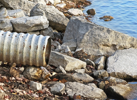 shore line: Large metal drain pipe on rocky shore line of lake Stock Photo