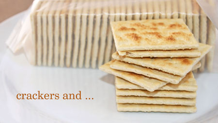 CRACKERS AND - Stack of crispy salted crackers on a plate to be enjoyed plain or with a topping
