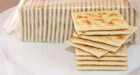 enjoyed: Stack of crispy salted crackers on a plate to be enjoyed plain or with a topping