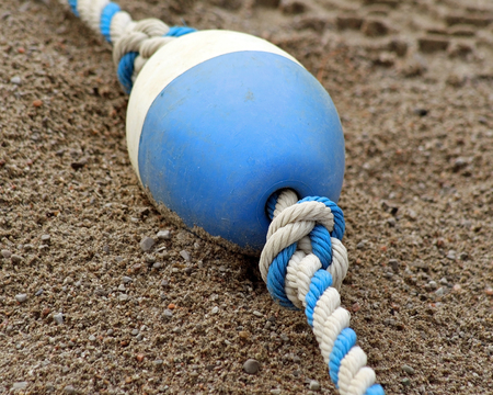 beach buoy: Blue and white plastic BUOY laying on sand at beach Stock Photo