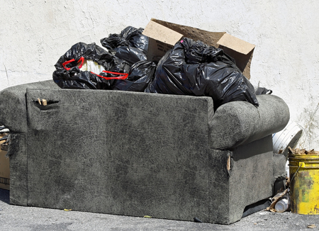 loveseat: Old worn furniture that has been discarded and left outdoors with garbage