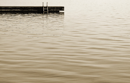 waters: Swimming dock with ladder at the edge of beautiful calm waters - Sepia Tone