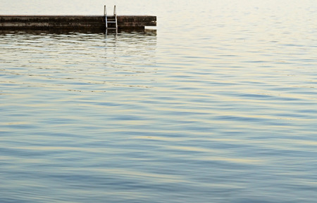 Swimming dock with ladder at the edge of beautiful calm waters