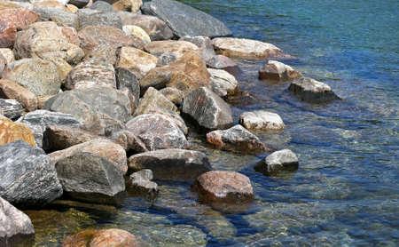shoreline: Rock bed along shoreline of clear blue lake waters Stock Photo