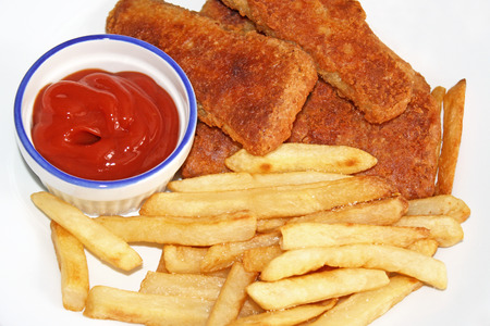 quick snack: Oven baked Fish Sticks with baked french fries cooked to a golden brown.  A side of zesty ketchup for dipping Stock Photo