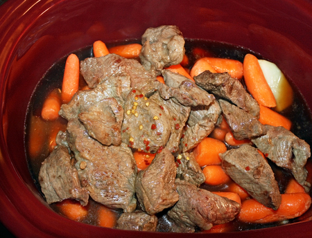 stewing: Layers of potatoes and carrots and browned stewing beef in a slow cooker with spices and added beef broth ready for cooking Stock Photo