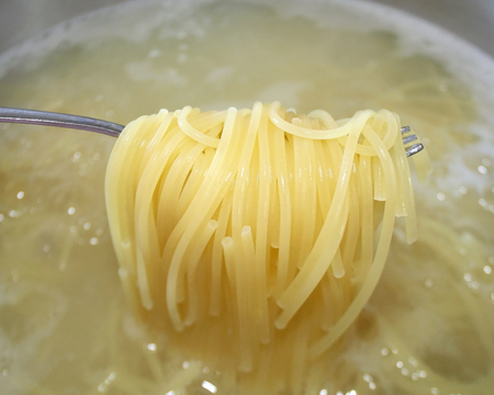 boiling: Cooked pasta noodles being lifted out of pot of boiling water with fork