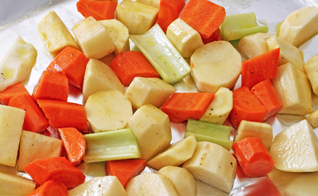 roasting pan: Potatoes, carrots, parsnips and celery seasoned with pepper and drizzled with oil ready for roasting