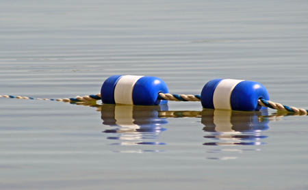 Buoys strung together and floating on surface of water