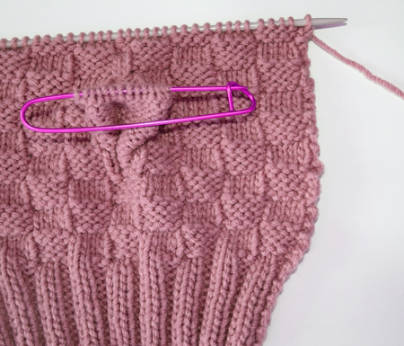 Basket weave pattern knitted on knitting needle in rose color wool.   Stitch holder in place marking off extra stitches to be knit later