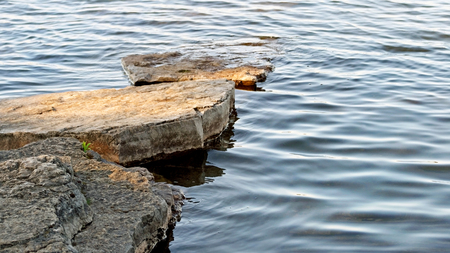 Stepping stones of flat natural rock leading out into beautiful lake Stock Photo