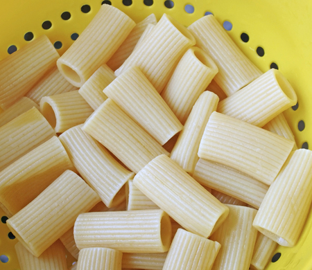 Drained and cooked Rigatoni pasta in a yellow plastic colander