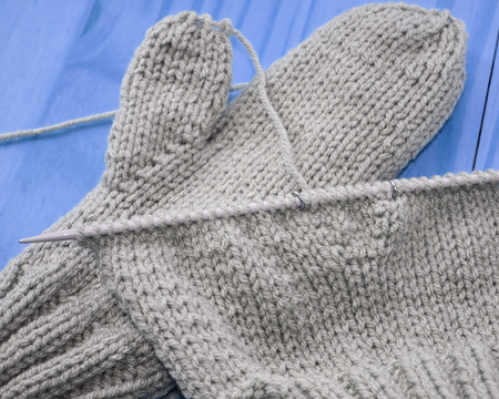 Gray worsted weight wool knitted on needle and one finished mitten in background