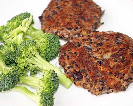 Homemade black bean burgers with a side of fresh broccoli