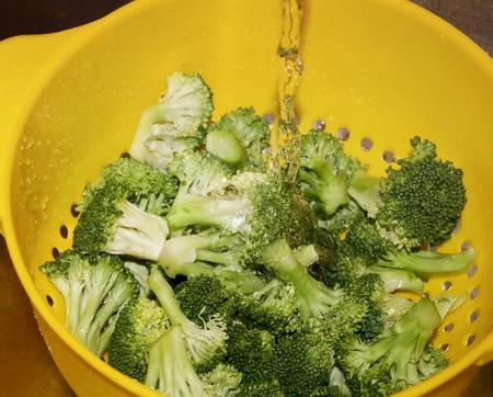 Fresh cut organic broccoli in yellow colander being rinsed under water