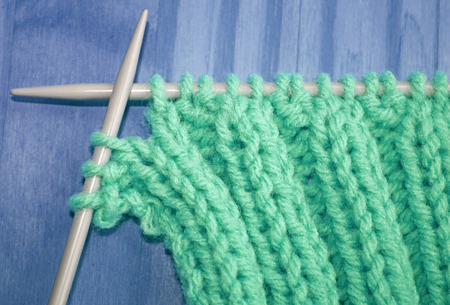 Knitted stitches on a pair of knitting needles Фото со стока