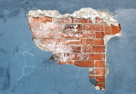 Brick wall with peeling paint and plaster in need of repair